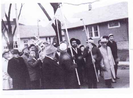 The procession makes its way to the synagogue.  Do you recognize anyone in the photo?